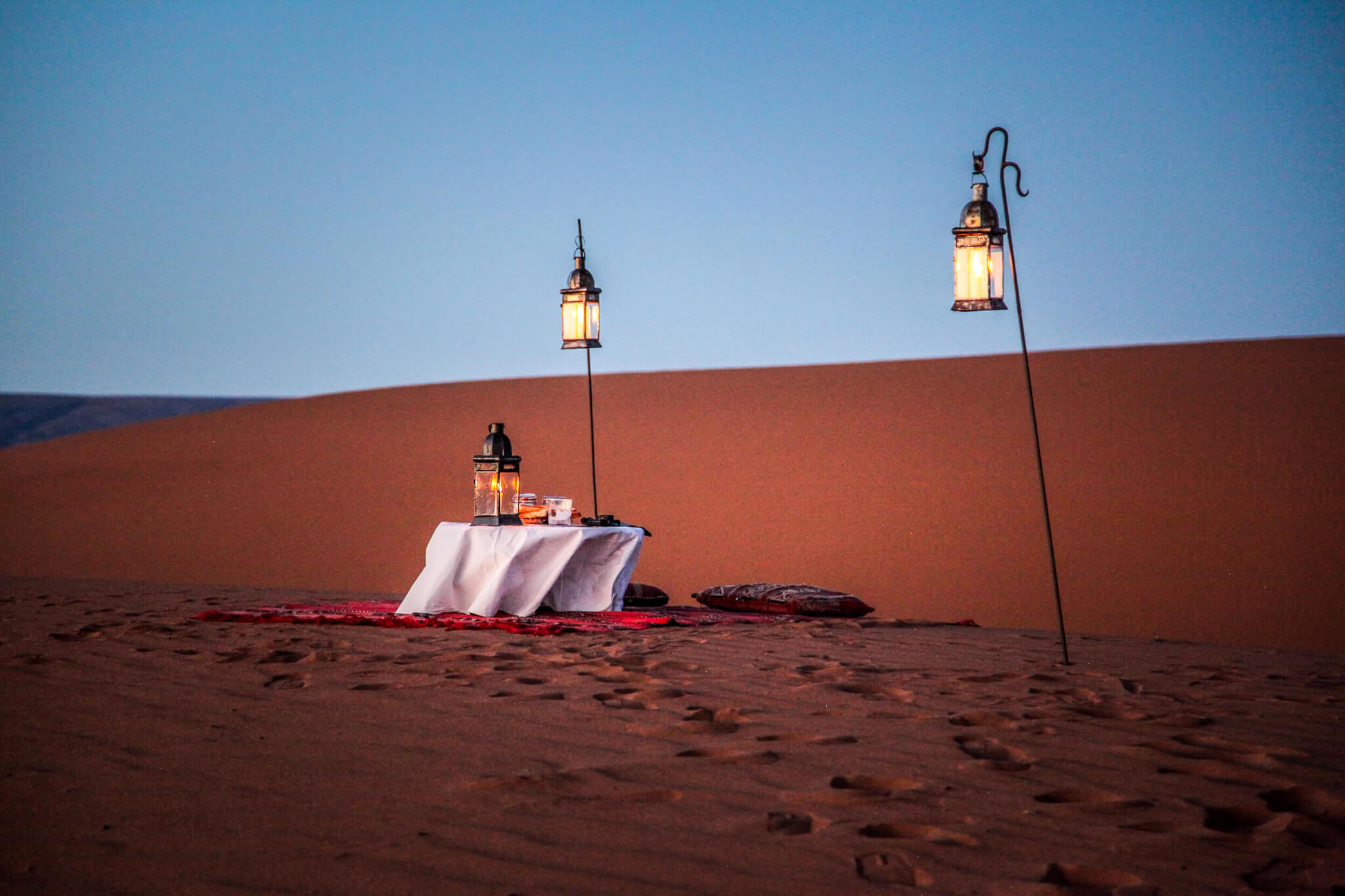 Sunset table with lanterns Dar Ahlam desert camp